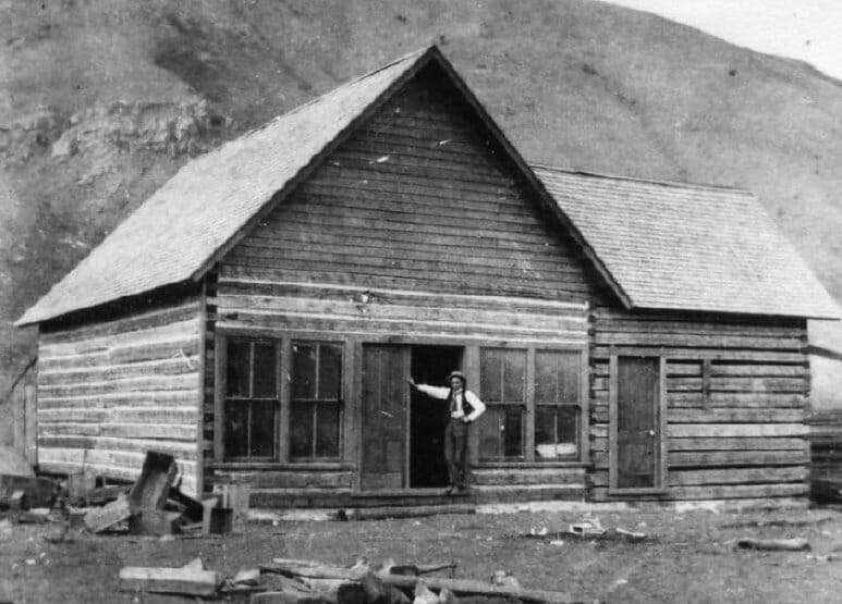 Vintage image of log cabin house with Teton mountains in background