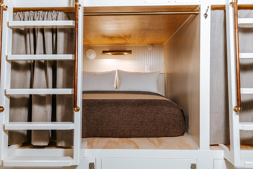 Bunk bed with reading lamp on and privacy curtain